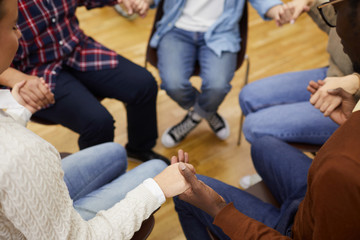 High angle closeup of unrecognizable people sitting ion circle and holding hands during support group meeting, cpy space