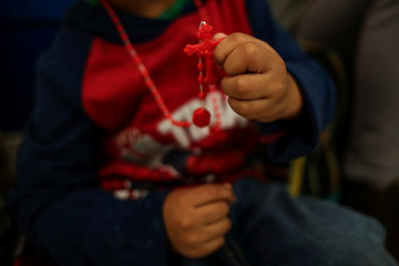 A Honduran boy shows his rosary at the airport after his family gave up their U.S. asylum claim and voluntarily return to Honduras, in Ciudad Juarez