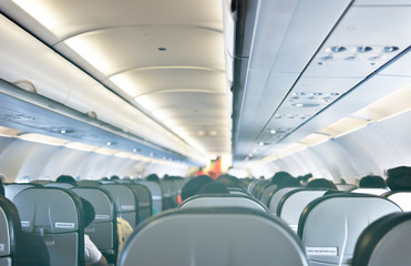 Interior of airplane with passengers sitting on seats, Travel concept. Selective focus. Vintage tone.