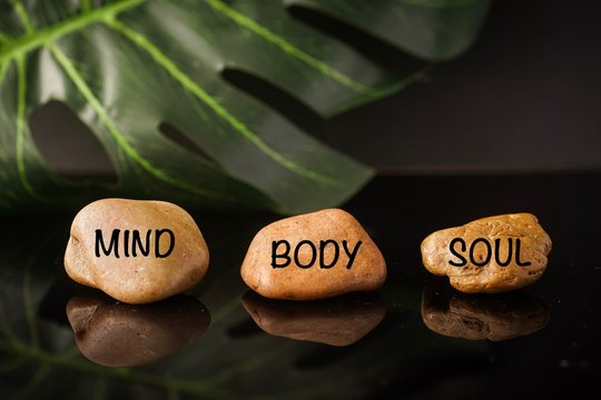 Zen Concept: Mind, Body and Soul wordings on stones against black background