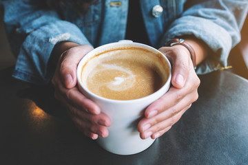 Closeup image of a woman holding a cup of hot latte coffee on the table