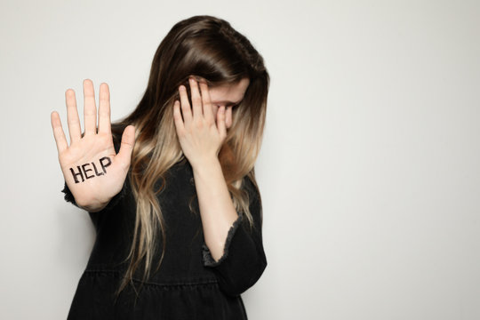 Young woman with word HELP written on her palm against light background, focus on hand. Space for text