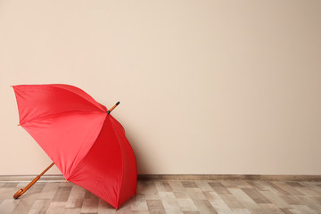 Wall Mural - Colorful umbrella on floor against beige wall. Space for text