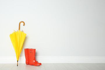 Wall Mural - Colorful umbrella and rubber boots on floor against white wall. Space for text