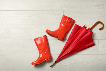 Wall Mural - Color umbrella and rubber boots on wooden floor, flat lay. Space for text