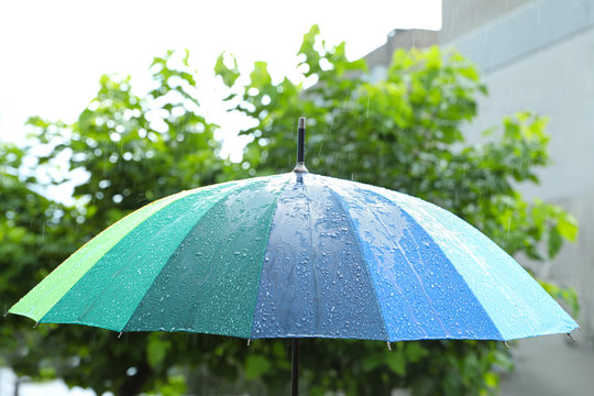 Open colorful umbrella outdoors on rainy day