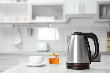 Modern electric kettle, cup and honey on wooden table in kitchen