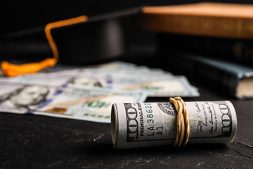 Dollar banknotes, student graduation hat and books on black table. Tuition fees concept