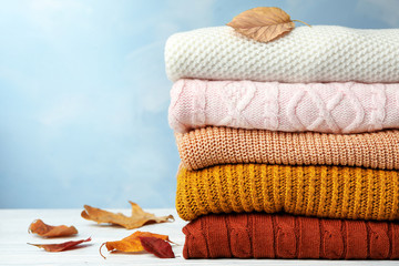Fototapete - Stack of warm clothes and autumn leaves on white wooden table against light blue background