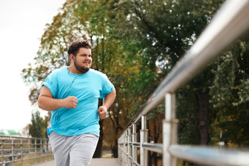 Obraz Young overweight man running outdoors. Fitness lifestyle - fototapety do salonu