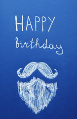 Words HAPPY BIRTHDAY and drawn beard with mustache on blue background, top view