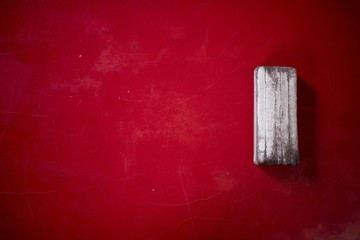 Shot of a red board with a blackboard eraser