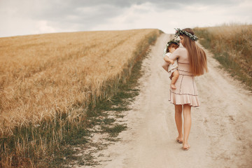 Family in a summer field. Mother in a wbrown dress. Cute little girl in a wreath
