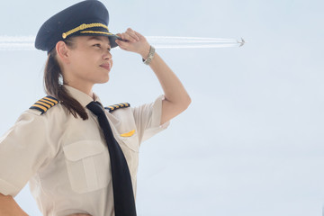 A female captain pilot standing next to an airplane at the airport. Wall mural