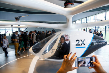 A visitor poses for a photo as he sits inside a Volocopter air taxi model in Singapore