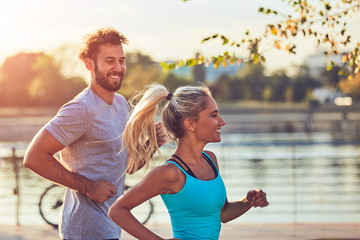 Modern woman and man jogging / exercising in urban surroundings near the river. Wall mural