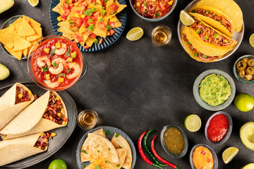 Mexican food, many dishes of the cuisine of Mexico, flat lay, shot from the top on a black background, forming a frame for copy space. Nachos, tequila, guacamole etc