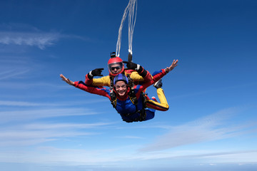 Tandem skydiving. An instructor and his woman-passenger are flying in the sky.