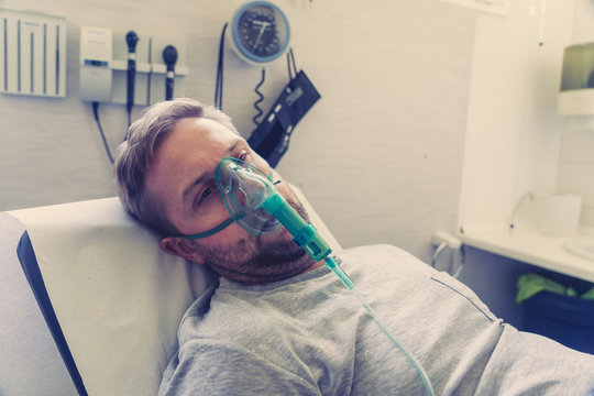 Sick man with oxygen mask in emergency room at hospital