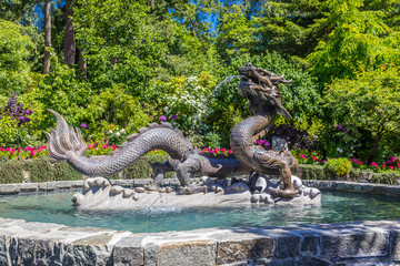 Dragon Statue at Butchart Gardens, Victoria Island, Canada in summer.  View of a fountain and staute with flowers and trees of the historic garden.