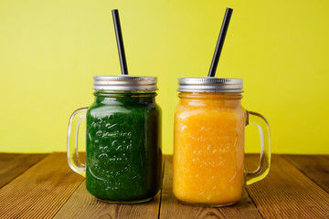 Two glasses with green and yellow detox smoothie with straws. Spinach and pumpkin smoothie on wooden table and yellow backgraund.