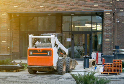 Skid loader stands in front of entrance to new multi-storey house and waits for garbage to be loaded into  bucket. Mini bulldozer waiting for cargo in front of porch