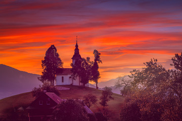 A beautiful shot of a silhouette of a church in the misty Alpine mountains with orange sunset sky in the background. Great for desktop wallpaper and backgrounds