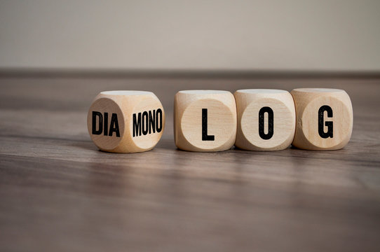 Cubes and dice on wooden background with the german words for dialogue and monologue - dialog und monolog