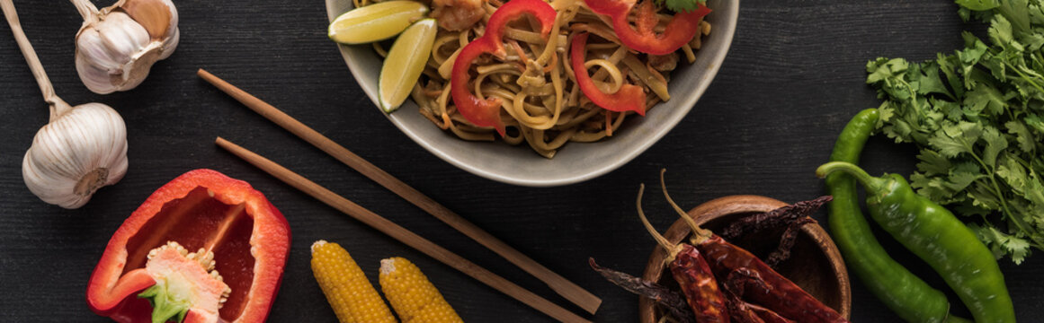 top view of tasty spicy thai noodles with garlic, parsley, corn, bell pepper, jalapenos near chopsticks on wooden grey surface, panoramic shot