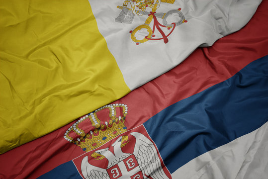 waving colorful flag of serbia and national flag of vatican city.