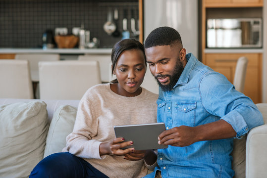 Young African American couple using a tablet together at home