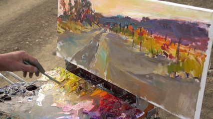 Closeup of painter artist working with oil paint on canvas on plein air. Art work, hobby and leisure