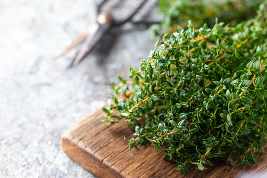 Bunch of fresh thyme herb on old wooden board