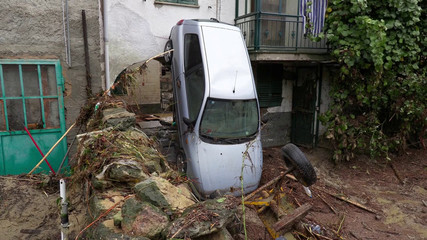 A car is seen resting on the bonnet leaning against an apartment building after flash floods in Castelletto D'Orba