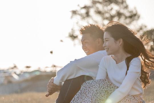 陽の当たる広場で遠くを見つめるカップル