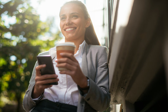 Young woman leaning on wall. Businesswoman drinking coffee and using phone.