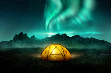Photo sur Plexiglas Camping A glowing yellow camping tent under a beautiful green northern lights aurora. Travel adventure landscape background. Photo composite.