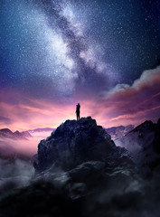 Fototapeta Night sky long exposure landscape. A man standing on a high rock watching the stars rise into the night sky. Photo composite. obraz