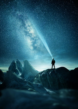 The milky Way lighting up the night sky with a man shining a flashlight towards it. Photo Composite.