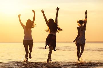 Three happy girls at caml sea beach and sunset