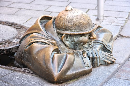 "BRATISLAVA, SLOVAKIA - AUGUST 9, 2012: Cumil the sewer worker statue in Bratislava, Slovakia. The artwork officially named ""Man at work"" was made in 1997 by artist Viktor Hulik."