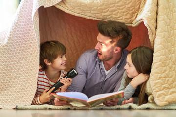Vater und Kinder mit Taschenlampe beim vorlesen