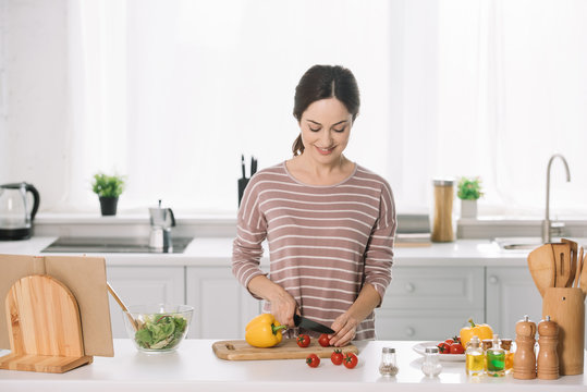 attractive young woman cutting fresh vegetables on chopping board