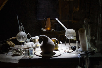 Set of alchemy bottles in laboratory of alchemist. Herb in old pots with dust on  the glass surface.Alchemy symbol and objects. Poison and elixir in glass jar. Set of vessel, ampulla, flask,drink.....