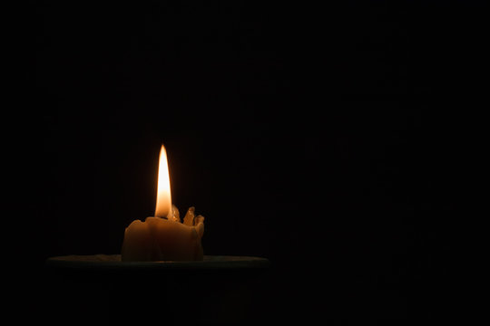 Burning candle in a black ceramic pot on a dark background. Concept of divination, magic, ritual. Copy space.