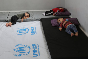 Displaced Kurdish babies, who fled violence with her families after a Turkish offensive in northeastern Syria, sleep in class at a public school in Hasakah