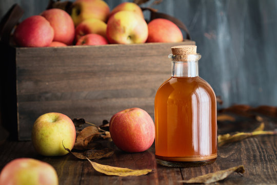 Apple cider vinegar with the mother, yeast and healthy bacteria, surrounded by fresh apples. Apple cider vinegar has long been used in naturopathy to treat things such as diabetes and high cholesterol