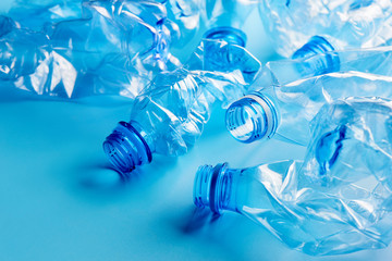 Empty crumpled plastic bottles pattern blue background. Recycling concept
