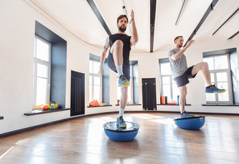 Two men athletes synchronously working out in interval training in the gym. Concept of wanting to be first and striving for a healthy strong body