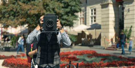 vintage style outdoor urban picture of  middle adult ages man with old photo camera taking picture in main square